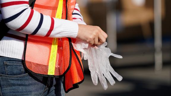 A volunteer puts on gloves before packing boxes of food outside the Second Harvest Food Bank in Irvine, California, on November 19.