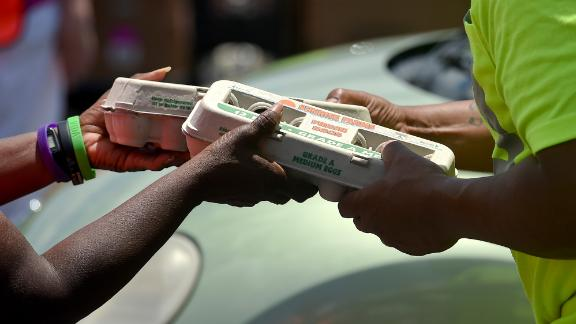 A volunteer hands two dozen eggs to a Helping Harvest employee to give to someone in their car in Muhlenberg, Pennsylvania, in June.