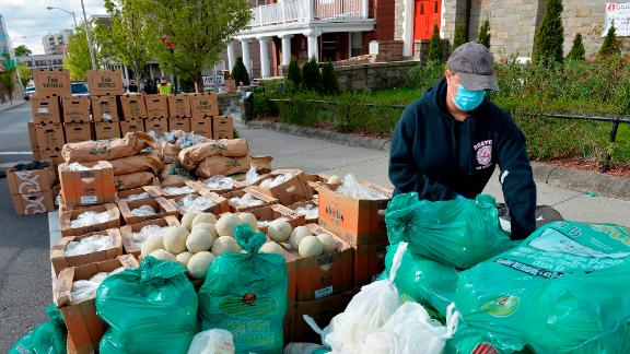 Volunteers load plastic bags with food in Everett, Massachusetts, during a weekly food pantry service run by Grace Ministries of the North Shore.