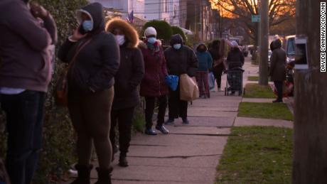 People wait in line to pick up food at Agatha House Foundation in the Bronx.