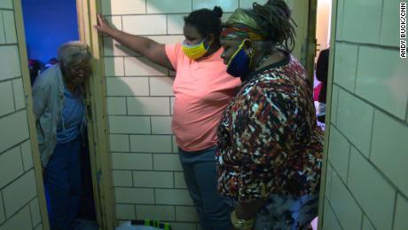 Regina Status, a la derecha, y su hija, de 13 años, le dan comida a su vecina, Mammie Vinning, en el Bronx.