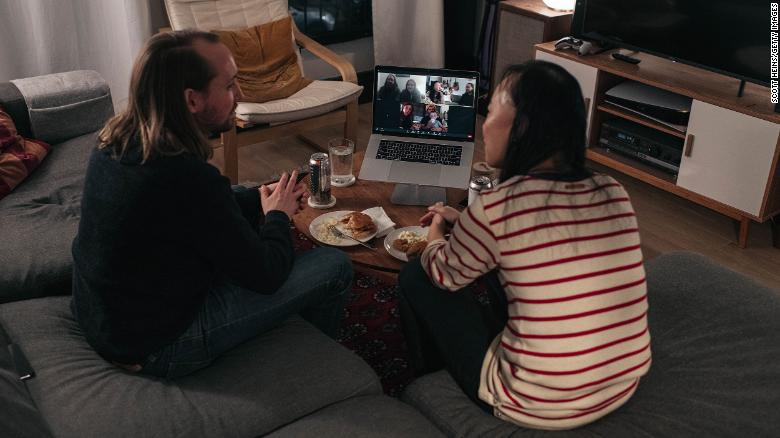 A couple celebrates Thanksgiving with friends by having dinner together over a Zoom video call on November 22, 2020, in New York.