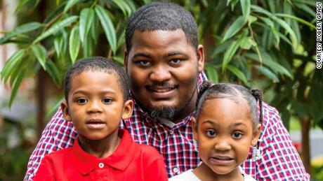 Chicago resident Robert Grady,  34, and his two children, 5-year-old Karen and 4-year-old Grayson, pose for Thanksgiving pictures in November 2019 at the Crystal Gardens Navy Pier in Chicago. Grady recently received LISC funding through the Jane Addams Resource Corporation to help him get back on his feet after being laid off from his manufacturing job due to Covid-19-related downsizing in July.
