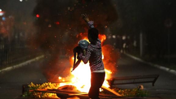 A man demonstrates in front of a bonfire during a protest against the death of Joao Alberto in Porto Alegre, Brazil on November 23, 2020.