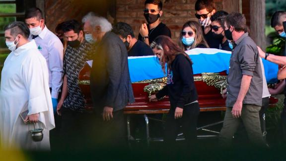 The coffin with the remains of late Argentine football legend Diego Armando Maradona is carried by his family and friends at the Jardin Bella Vista cemetery, in Buenos Aires province, on November 26, 2020. - Argentine football legend Diego Maradona -who died of a heart attack on the eve, at the age of 60- will be laid to rest where his parents have been buried. (Photo by RONALDO SCHEMIDT / AFP) (Photo by RONALDO SCHEMIDT/AFP via Getty Images)