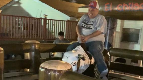 Lopez rides a mechanical bull.