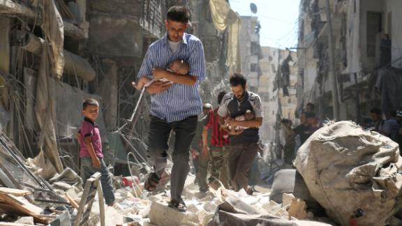 Syrian men carrying babies make their way through the rubble of destroyed buildings following a reported air strike on the rebel-held Salihin neighborhood of the northern city of Aleppo, on September 11, 2016.