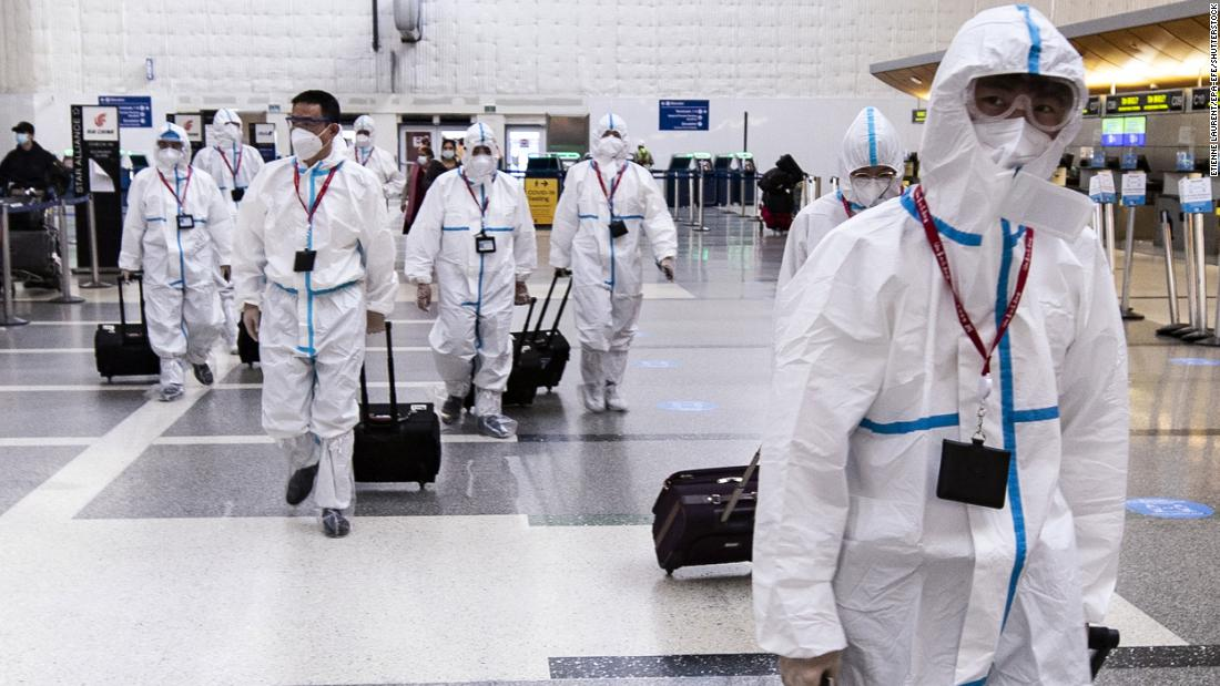 Airline crew members wearing protective suits arrive at Los Angeles International Airport on November 24.
