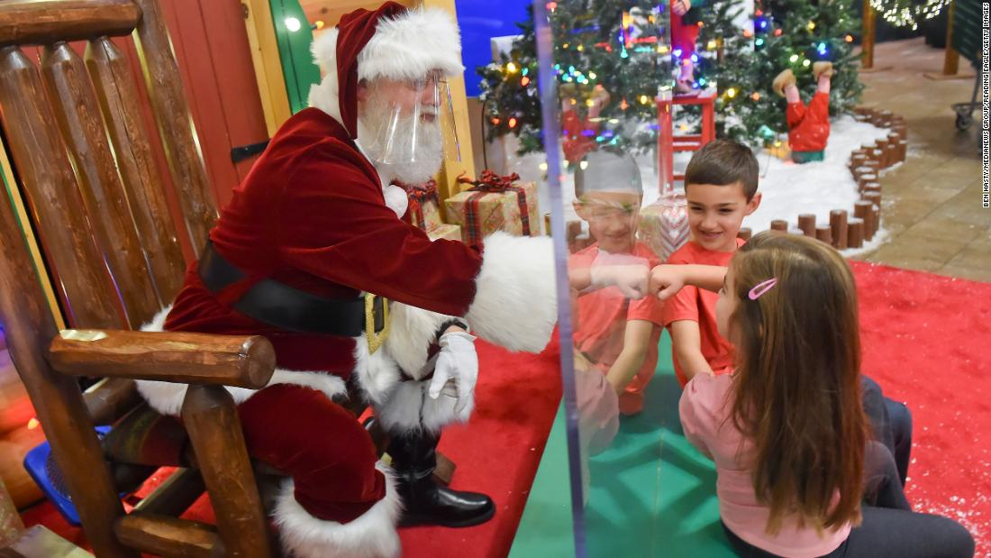 Cali Hammer fist-bumps Santa, who was behind a plexiglass partition at a Cabela's store in Tilden Township, Pennsylvania, on November 20.