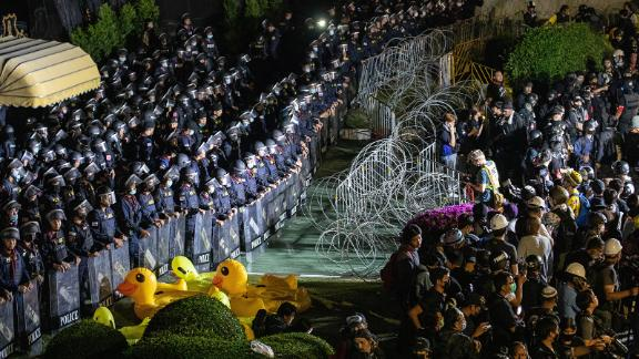 Riot police stand guard behind barbed wires and inflatable yellow ducks during an anti-government demonstration in the Thai capital.