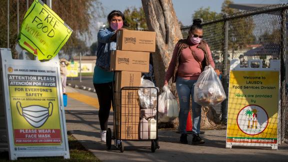 Two women take home free meals after waiting in a long line at a high school in South Gate, California, on November 25.