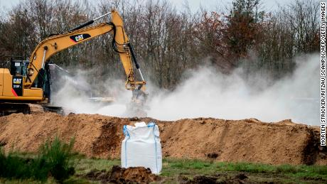 A bag of calcium oxide is seen in the foreground as an excavator buries dead mink in ditches in a military area near Holstebro, Denmark on Monday, November 9, 2020.