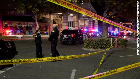 Sacramento police officers stand outside the mall Friday evening following the shooting, which left two people dead.