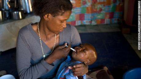 A mother in Lesotho, pictured here in 2007, gives her baby a dose of HIV medicines. In the first half of 2021, a pediatric formulation of dolutegravir, a drug recommended as first-line HIV treatment by the World Health Organization, will become available in some countries.