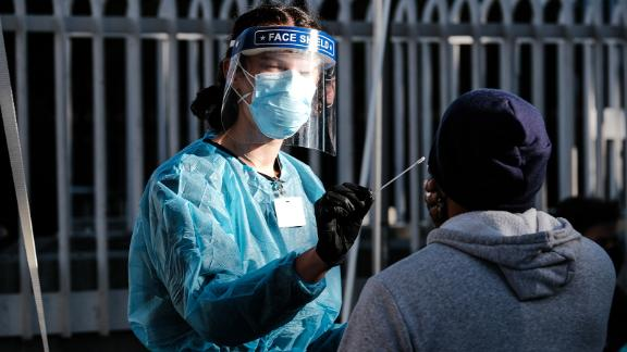 A healthcare worker administers a test at a Covid-19 testing tent outside a Bay Area Rapid Transit (BART) station in the Mission District of San Francisco, California, U.S., on Monday, Nov. 30, 2020. UCSF and the Latino Task Force held post-holiday Covid-19 testing in four of the most affected neighborhoods in San Francisco, ABC7 San Francisco reports. Photographer: David Odisho/Bloomberg via Getty Images