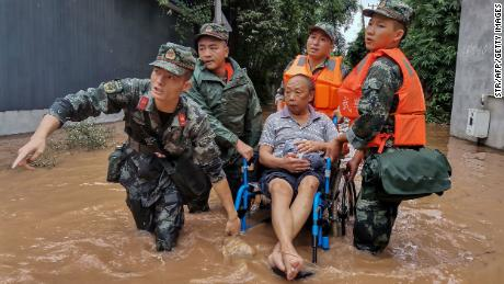 A resident is evacuated from a flooded street in Meishan in China's southwestern Sichuan province.