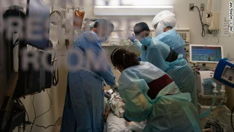 FILE - In this Nov. 19, 2020, file photo, EMT Giselle Dorgalli, second from right, looks at a monitor while performing chest compression on a patient who tested positive for coronavirus in the emergency room at Providence Holy Cross Medical Center in the Mission Hills section of Los Angeles. Amid the coronavirus resurgence, states have begun reopening field hospitals to handle an influx of sick patients that is pushing health care systems — and their workers — to the breaking point. Hospitals are bringing in mobile morgues. And funerals are once again being livestreamed or performed as drive-by affairs. (AP Photo/Jae C. Hong, File)