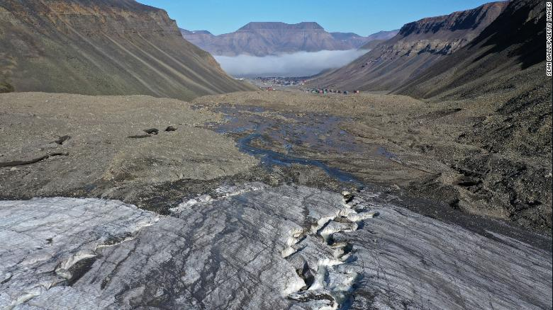 In this aerial view from a drone, taken in July 2020, meltwater carves a winding channel through the melting Longyearbreen glacier during a summer heat wave near Longyearbyen, Norway.