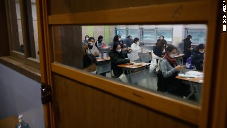 Students wearing face masks wait for the start of the annual college entrance examination amid the coronavirus pandemic at an exam hall in Seoul, South Korea, on December 3, 2020.