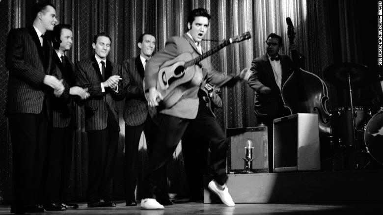 O cantor e músico americano Elvis Presley gira seus quadris enquanto se apresenta com sua banda no palco durante sua segunda aparição no & quot; The Ed Sullivan Show, & quot; em 28 de outubro de 1956.