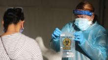 SAN FERNANDO, CALIFORNIA - DECEMBER 2: A healthcare worker holds a specimen bag at a walk-up Covid-19 testing site on December 2, 2020 in San Fernando, California. California reported 20,759 new coronavirus cases today, a one-day record for the state, amid a new limited stay-at-home order in Los Angeles County. (Photo by Mario Tama/Getty Images)