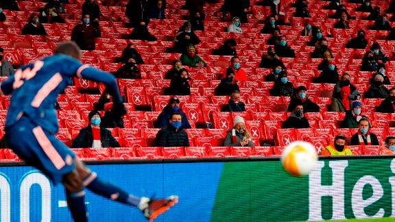 Supporters wearing protective face coverings to combat the spread of the coronavirus, watch as a corner kick is taken during the UEFA Europa League 1st Round Group B football match between Arsenal and Rapid Vienna at the Emirates Stadium in London on December 3, 2020. - Areas of England in tier two zones are now allowed up to 2,000 fans with Arsenal welcoming back supporters for the first time tonight since a four-week lockdown was lifted. (Photo by Adrian DENNIS / AFP) (Photo by ADRIAN DENNIS/AFP via Getty Images)