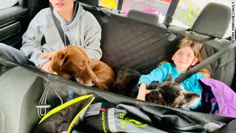 Payton and Rebecca Marchessault, holding their dogs during their road trip from Georgia to Alaska.