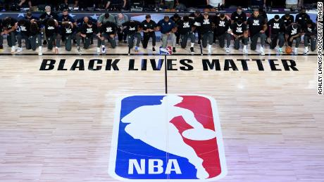Members of the New Orleans Pelicans and Utah Jazz kneel before a Black Lives Matter logo before the start of their game at HP Field House at ESPN Wide World Of Sports Complex on July 30, 2020 in Reunion, Florida.