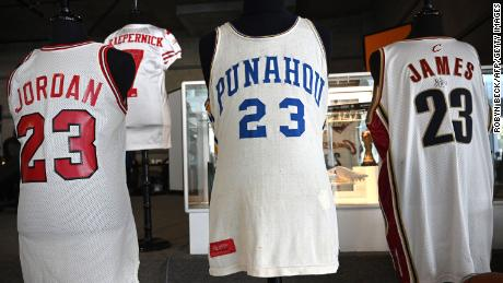 Michael Jordan's 1984 signing day Chicago Bulls jersey is displayed beside President Barack Obama's high school basketball jersey and a Cleveland Cavaliers jersey worn by LeBron James.