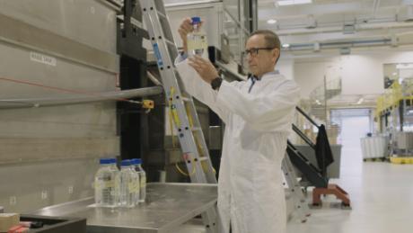 Joerg Hess ، مدیر عامل شرکت Aquaporin A / S ، آب فیلتر شده را با استفاده از غشای آکواپورین بررسی می کند.