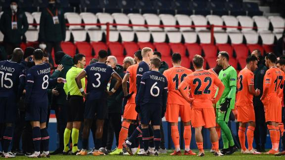 Romanian referee Ovidiu Hategan (in yellow) talks to Istanbul Basaksehir's staff members during the UEFA Champions League group H football match between Paris Saint-Germain (PSG) and Istanbul Basaksehir FK at the Parc des Princes stadium in Paris, on December 8, 2020. - Paris Saint-Germain's decisive Champions League game with Istanbul Basaksehir was suspended today in the first half as the players walked off amid allegations of racism by one of the match officials. The row erupted after Basaksehir assistant coach Pierre Webo, the former Cameroon international, was shown a red card during a fierce row on the touchline with staff from the Turkish club appearing to accuse the Romanian fourth official of using a racist term. (Photo by FRANCK FIFE / AFP) (Photo by FRANCK FIFE/AFP via Getty Images)