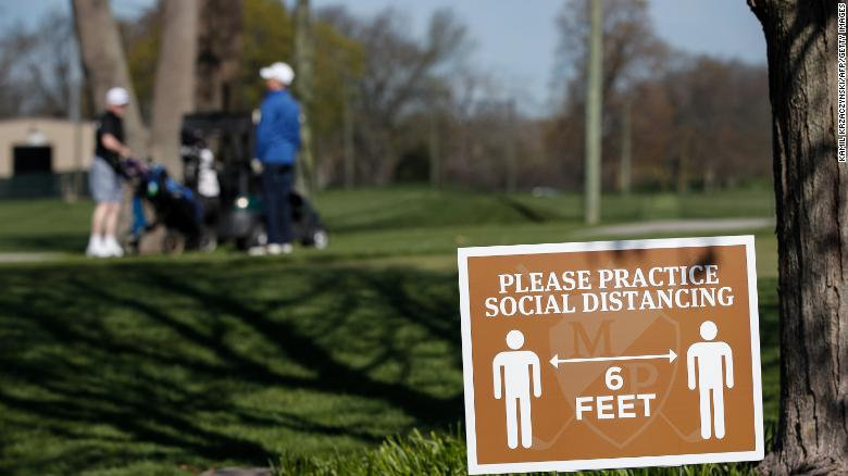 A sign informs golfers to practice social distancing at the Mt. Prospect Golf Club in Mt. Prospect, Illinois.