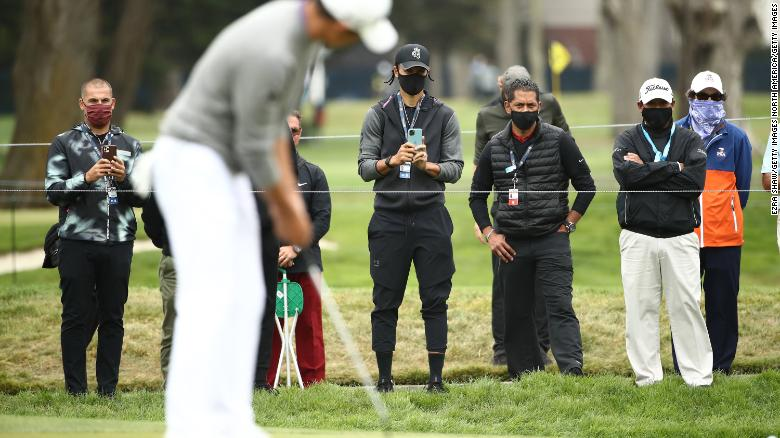 NBA athlete Stephen Curry of the Golden State Warriors takes a photo as Collin Morikawa of the United States putts on the seventh green during the final round of the 2020 PGA Championship.