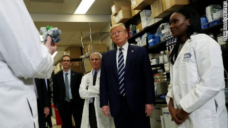 Drs. Anthony Fauci, left, and Kizzmekia Corbett, right, flank President Donald Trump at the NIH Vaccine Research Center in March.