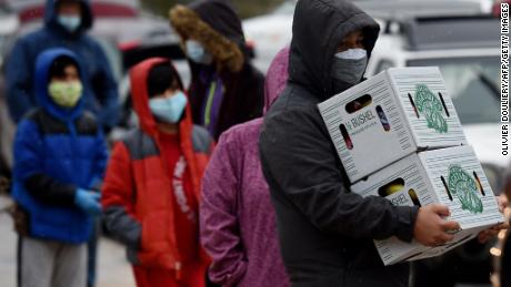 People carry food donated by volunteers from the Baltimore Hunger Project outside of Padonia International Elementary school on December 4, 2020 in Cockeysville, Maryland.