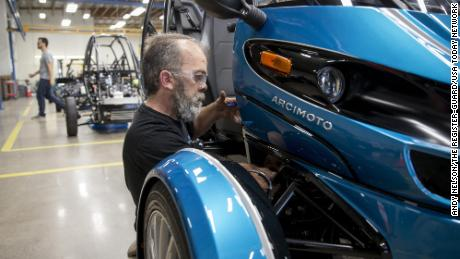 Mike Dunphy installs lower dash panels on an Arcimoto vehicle.