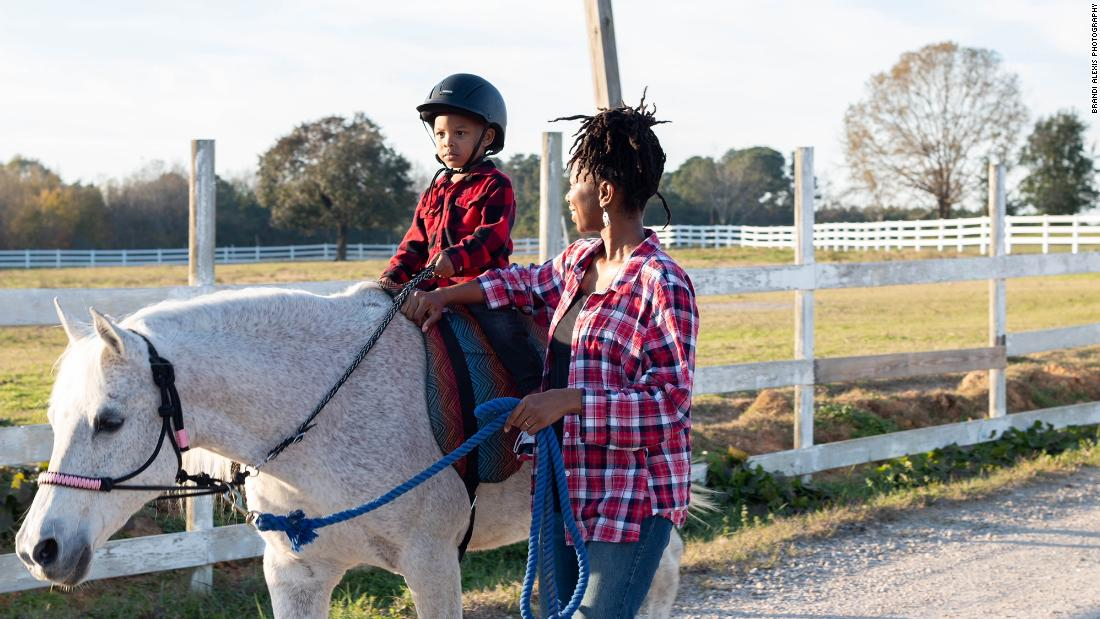 Caitlin Gooch instructs Sevyn on how to ride a horse.