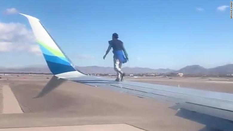 A man was taken into custody after he climbed onto the wing of a airplane preparing to takeoff in Las Vegas