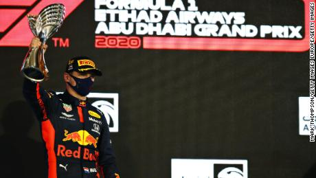 Verstappen stands on the podium with his trophy.