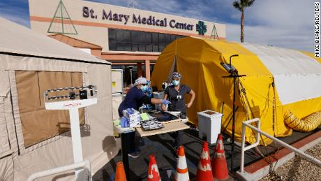 ER tech Brenda de la Cruz (R) and RN Janet Hays works outside St Mary Medical Center in the triage tents as they handle the overflow at its 200-bed hospital during the coronavirus outbreak in Apple Valley, California, December 8, 2020.
