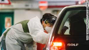 Medical workers administer antigen tests at Lanxess arena parking lot in Cologne, Germany, on December 14.