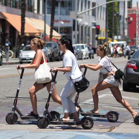 Young women ride shared electric scooters in Santa Monica, California, on July 13, 2018. - Cities across the U.S. are grappling with the growing trend of electric scooters which users can unlock with a smartphone app. Scooter startups including Bird and Lime allow riders to park them anywhere that doesn't block pedestrian walkways but residents in some cities, including Los Angeles, say they often litter sidewalks and can pose a danger to pedestrians. (Photo by Robyn Beck / AFP) (Photo by ROBYN BECK/AFP via Getty Images)