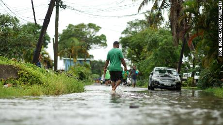Residents wade through the flooded streets in Fiji's capital city of Suva on December 16, 2020, ahead of super Cyclone Yasa.