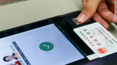 """A student scanning their second-generation """"smart"""" ID card at an exam site in July 2020 in Nanchang city."""