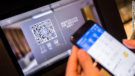 """A Chinese man uses an """"electronic ID card"""" in a mobile payment app to check into a hotel in Hangzhou in April 2017. The blurred QR code was not added by CNN."""