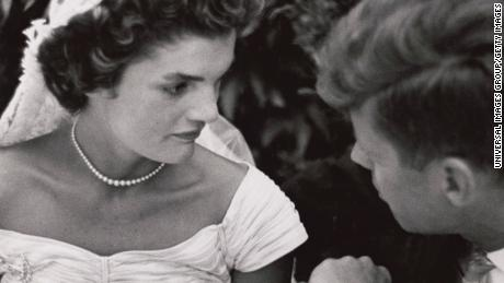 Jacqueline Bouvier Kennedy and Sen. John F. Kennedy talk at their wedding reception in 1953.