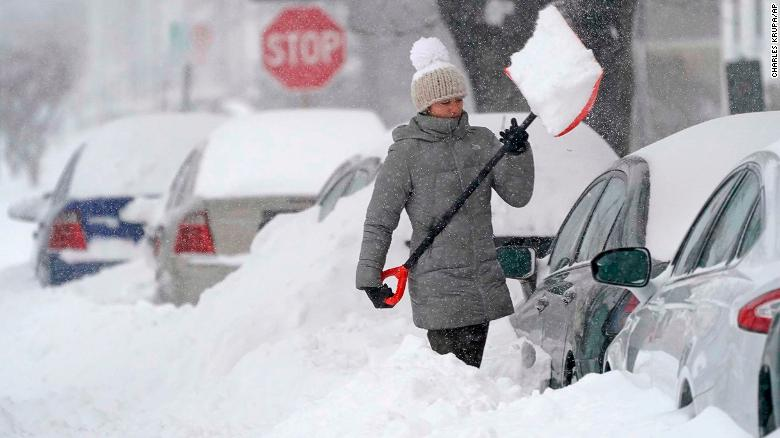 A woman tosses a shovel full of snow while digging out her car on Dec. 17, 2020, in Manchester, New Hampshire.