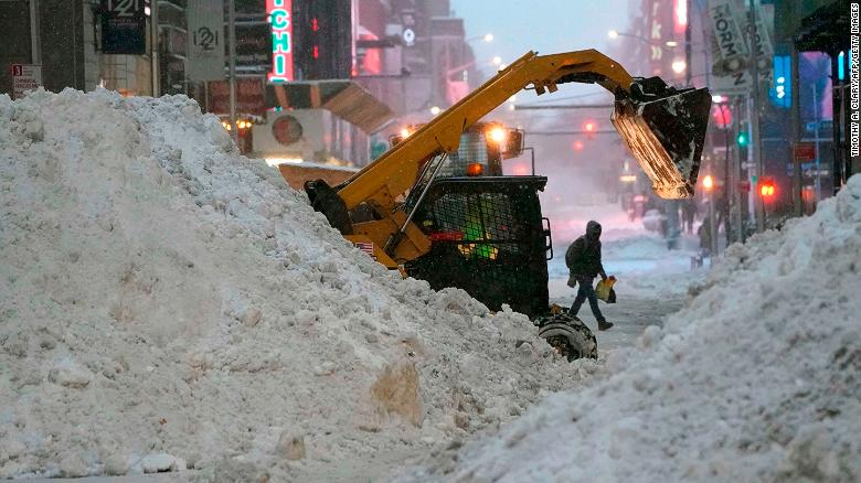 A snowplow pushes snow near Times Square on December 17, 2020 in New York, the morning after a powerful winter storm hit the US northeastern states.