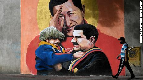 A mural depicting Venezuelan late President Hugo Chavez (C) saluting and Venezuelan President Nicolas Maduro (R) holding a child in Caracas on December 9, 2020.