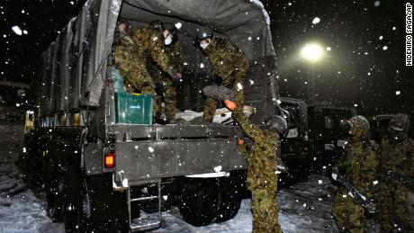 Japan Self-Defense Forces personnel prepare food and water for people stranded on the Kantsu Expressway on 17 December.